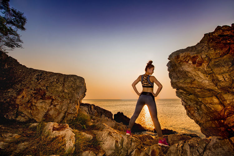 Rear view of young woman with hands on hip standing at rocky beach against clear sky during sunset