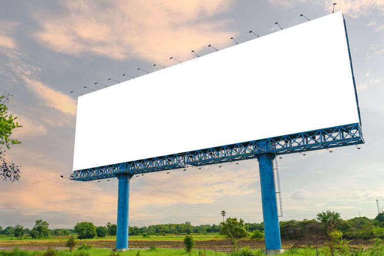 Low angle view of sign board against sky during sunset