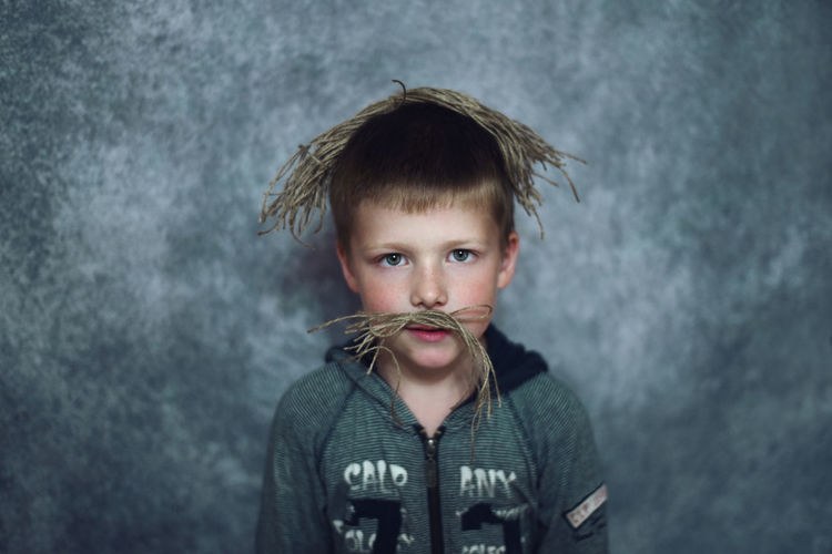 Portrait of boy wearing strings against wall