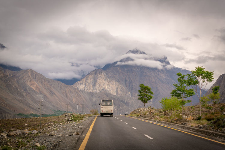 A bus passing the road over looking a beautiful snowy mountain