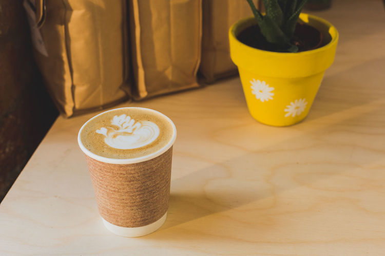 Latte Art coffee on wooden table with yellow plant pots Cardboard Cardboard Box Close-up Coffee Coffee Cup Coffee Shop Coffee Time Day Drink Espresso Food And Drink Froth Art Frothy Drink Latte Latte Art Latteart No People Plant Life Refreshment Table Takeaway Takeaway Coffee Wood Table Wooden Yellow