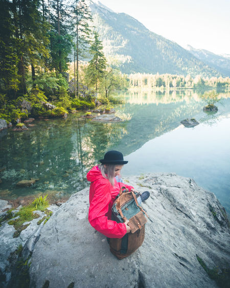 Woman With Backpack Sitting At Lakeshore Against Mountains
