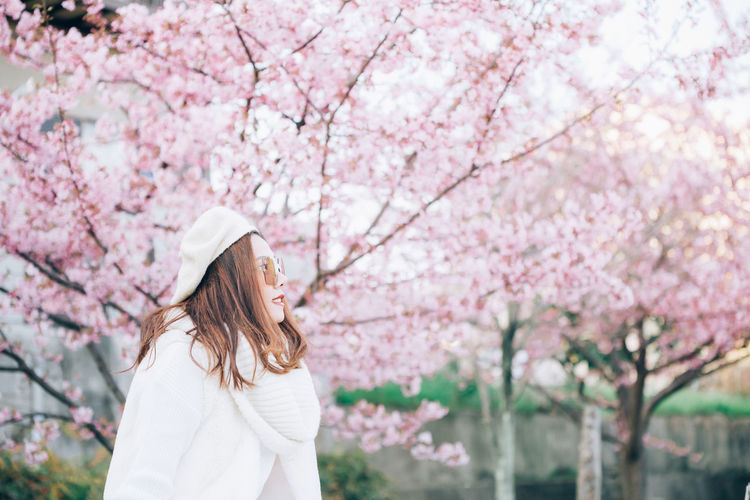 Low angle view of woman standing by pink cherry blossom tree