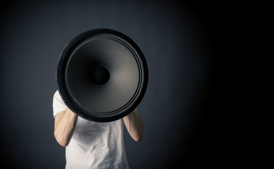 Speak a little bit louder ! Dark Demo Democracy Man URGENT Black Background Day Indoors  Information Loudspeaker Male Message Metaphor One Person People Speaker Speaking Studio Photography Studio Shot Symbolic  Technology