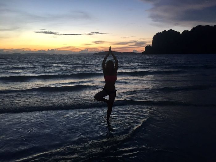 Silhouette woman practicing tree pose on shore at beach during sunset