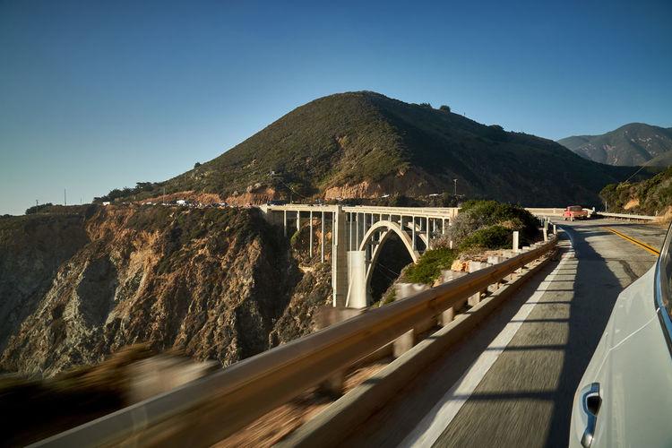 Bridge over mountain against clear sky