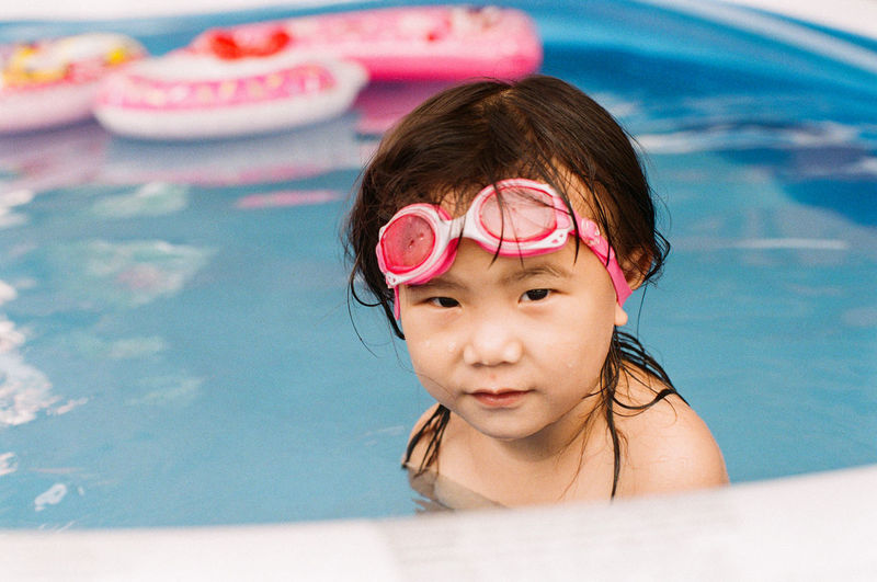 Asian little girl swimming in the pool. Child Childhood One Person Portrait Headshot Real People Pool Leisure Activity Swimming Pool Innocence Front View Lifestyles Girls Cute Females Eyewear Swimming Asian  Kids Girl Swimming Water Swimming Goggles Glasses Innocence Fun Looking At Camera Smiling Swimming Innocence