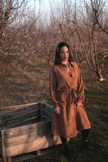 Portrait of woman standing by bare tree