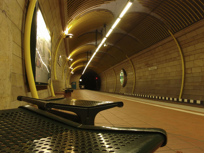 Absence Arch Architectural Column Architecture Built Structure Ceiling Diminishing Perspective Direction Empty Flooring Illuminated In A Row Indoors  Lighting Equipment No People Pattern Public Transportation Seat Subway Table Tunnel Underpass