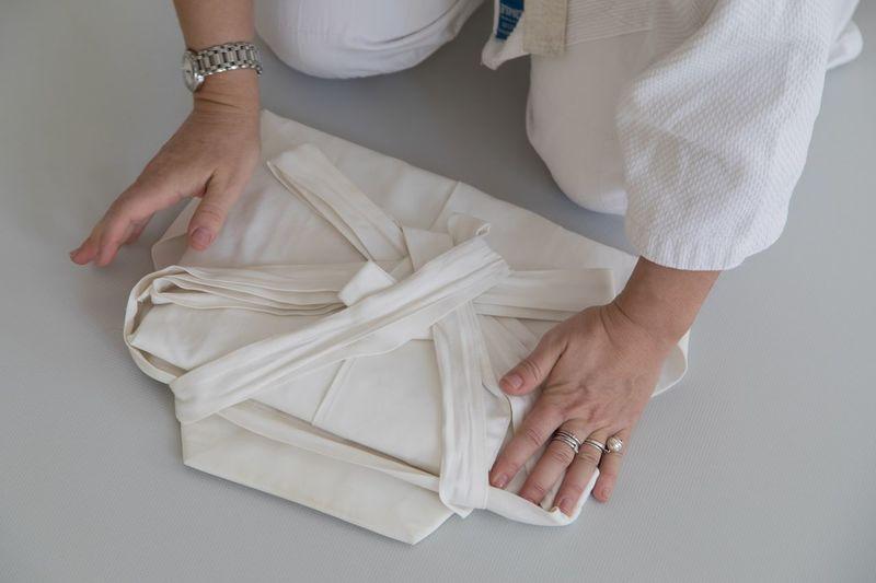 Midsection of woman folding kimono on floor