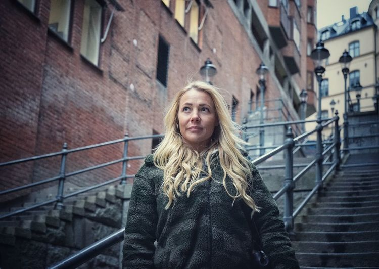 Portrait of woman against railing in city