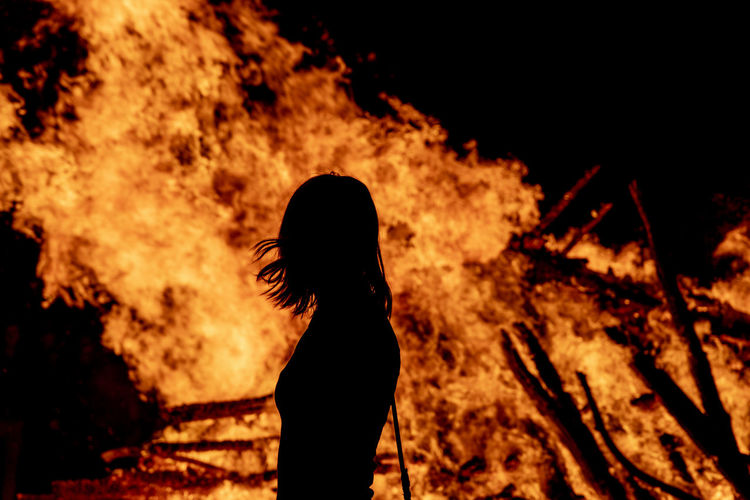 Silhouette woman standing by bonfire on field at night