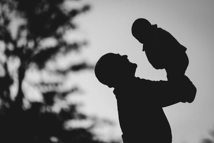 Low angle view of silhouette boy against sky