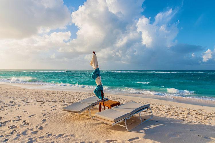 Sunbeds beach against sky