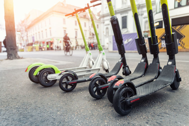 Close-up of push scooters on road