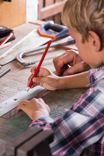 Midsection of boy learning carpentry