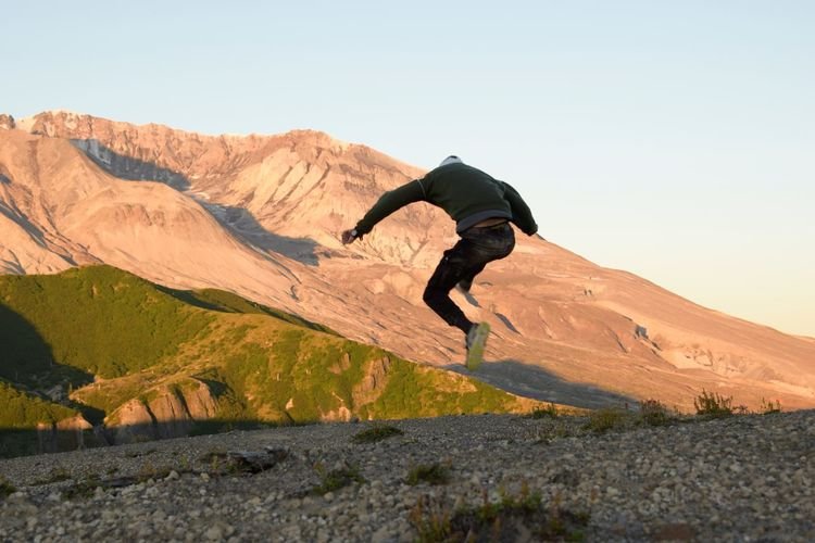 Man jumping on mountain against clear sky
