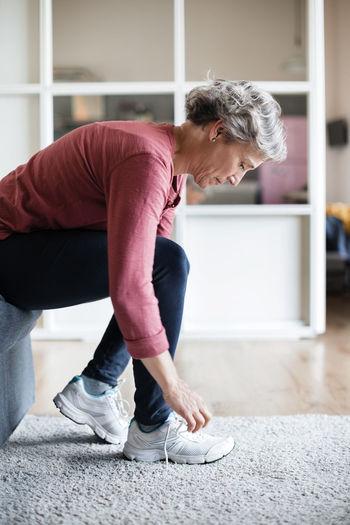 Full length of senior woman lying on floor at home