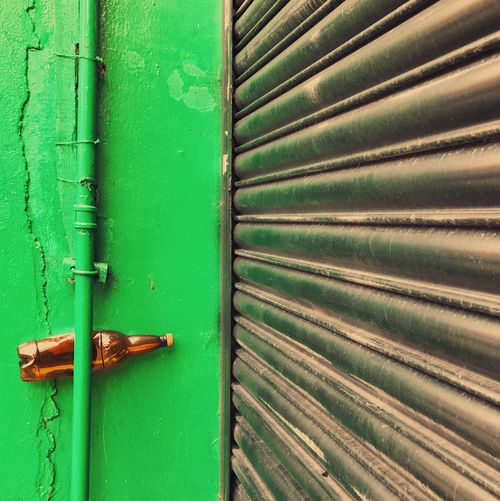 Bottle stuck in pipe by closed shutter on green wall