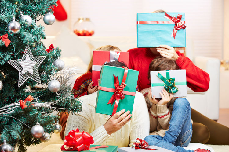 Cheerful family covering face while sitting by christmas tree on sofa at home