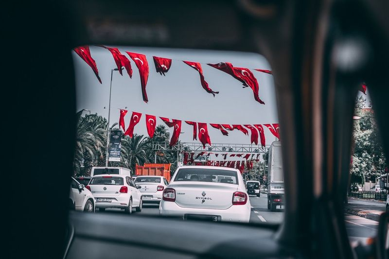 Red flags in city seen through car windshield