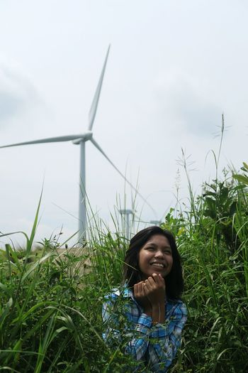 Smiling woman standing amidst plants against windmill and sky