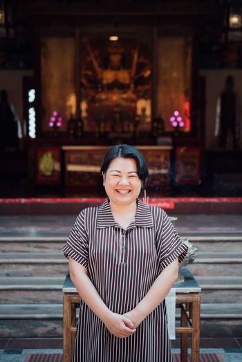 Portrait of smiling woman standing at temple