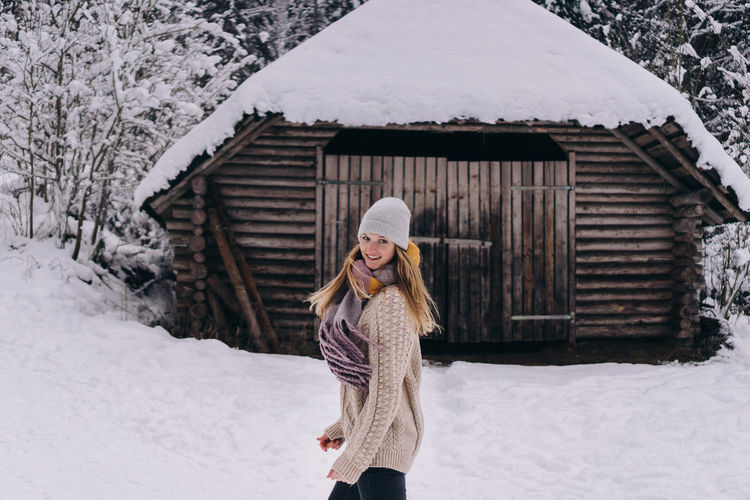 Full length of woman standing in front of  snow covered house