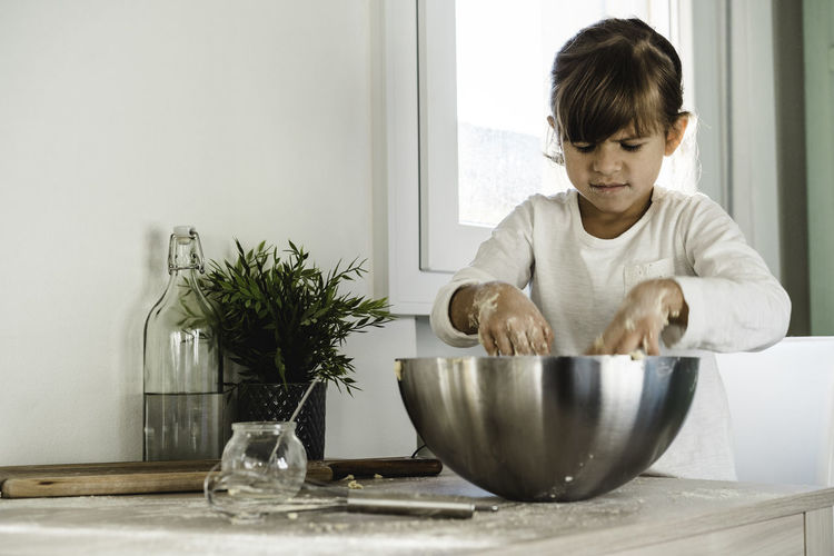 Girl kneading dough in bowl at home