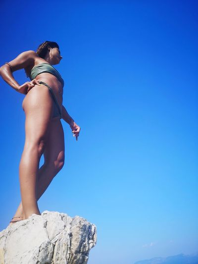 Low angle view of woman standing on cliff against blue sky