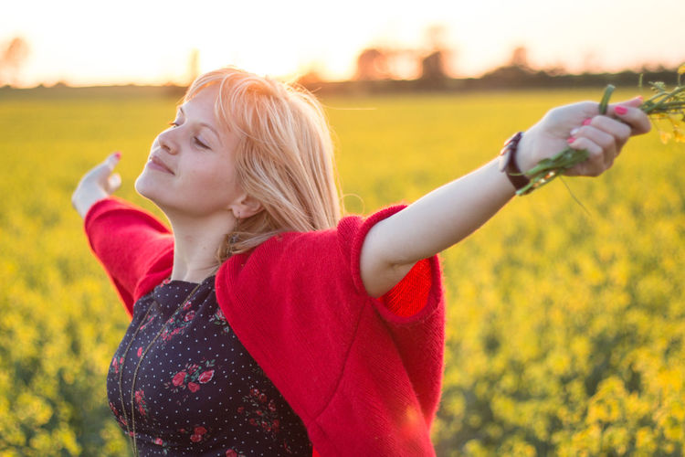 Beautiful young woman with arms outstretched standing against rap field