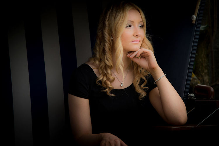 Young woman looking away while sitting against black background