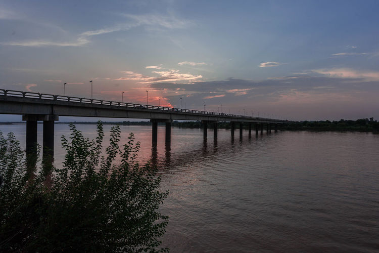 Bridge over river against sky during sunset