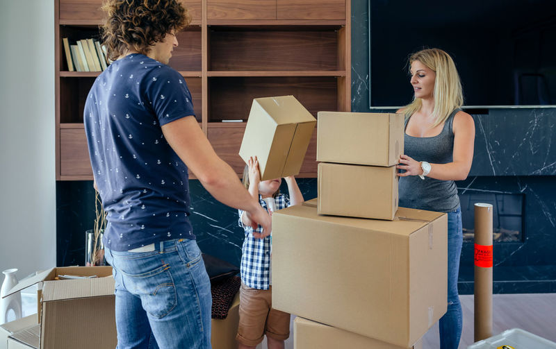 Aerial view of unrecognizable father and son assembling moving box Family Fun Happiness Happy Horizontal Man Moving Unpacking Woman Apartment Boxes Boy Cardboard Home Interior House Indoors  Lifestyles Living Room New Home Packing Placing Real People Relocating Three People Togheter
