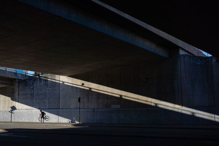 Man with bicycle walking under bridge in city