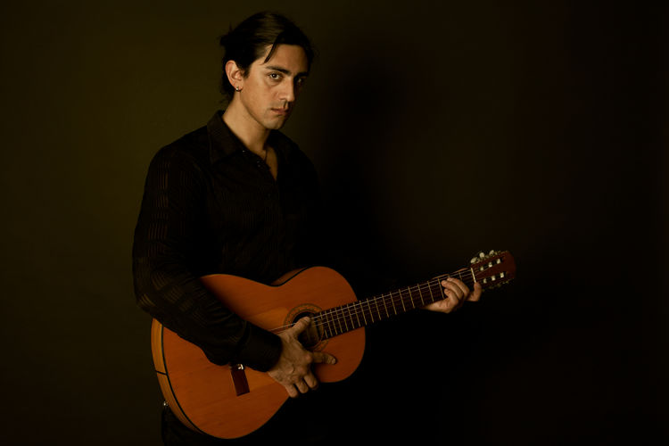 Portrait of young man playing guitar against black background