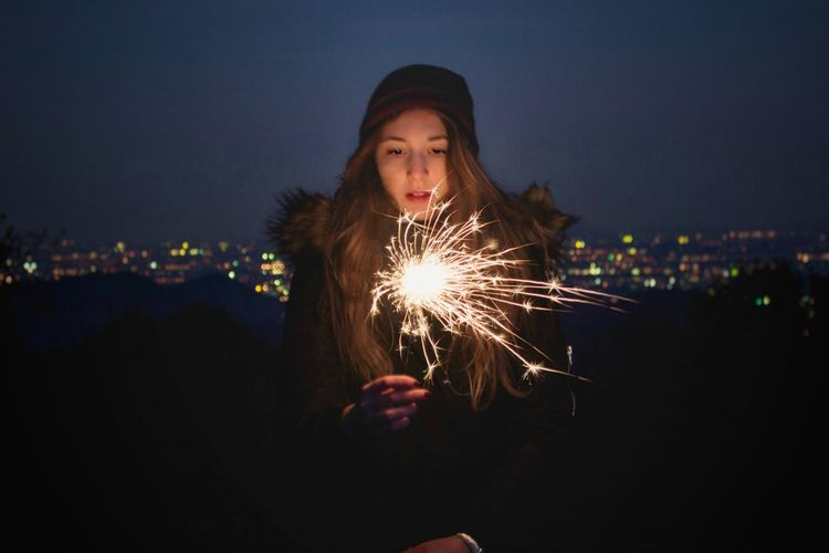 Young woman holding illuminated sparkler at night