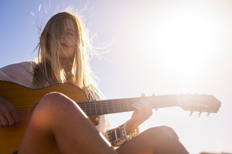 beautiful young woman play guitar under the sun Beautiful Woman Blond Hair Day Guitar Human Face Legs Leisure Activity Lifestyles Long Hair Music Musical Instrument Musician One Person Outdoors People Playing Plucking An Instrument Real People Relaxing Moments Sitting Sky Sunlight Sunny Day Young Adult Young Women