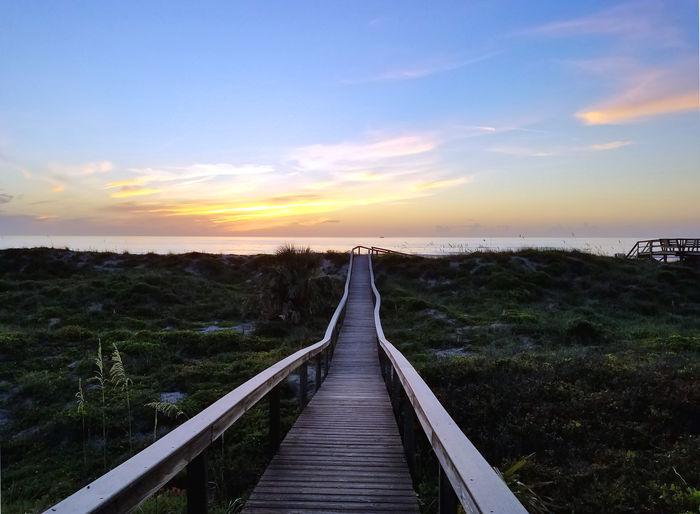 Footbridge over to sea during sunset