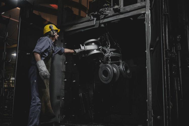 Man working over metallic machine in industry