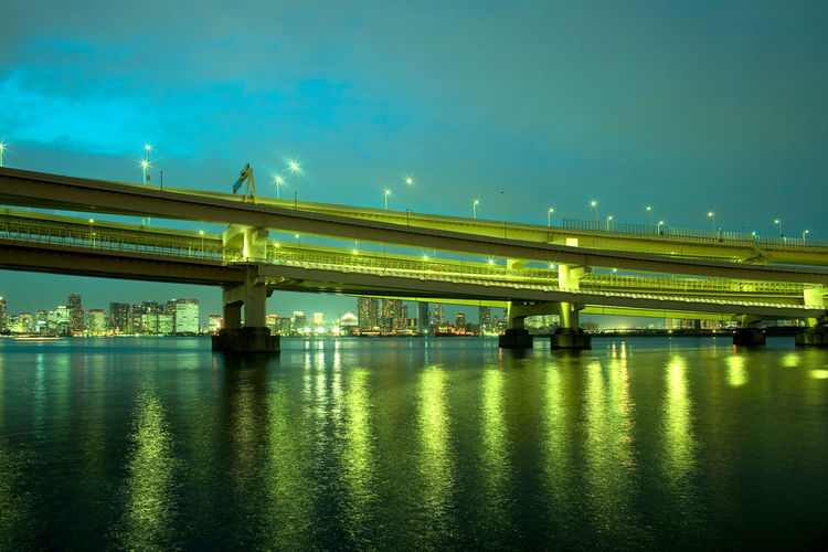 Bridge over river against sky in city at night