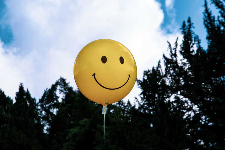 Low angle view of yellow balloons against sky