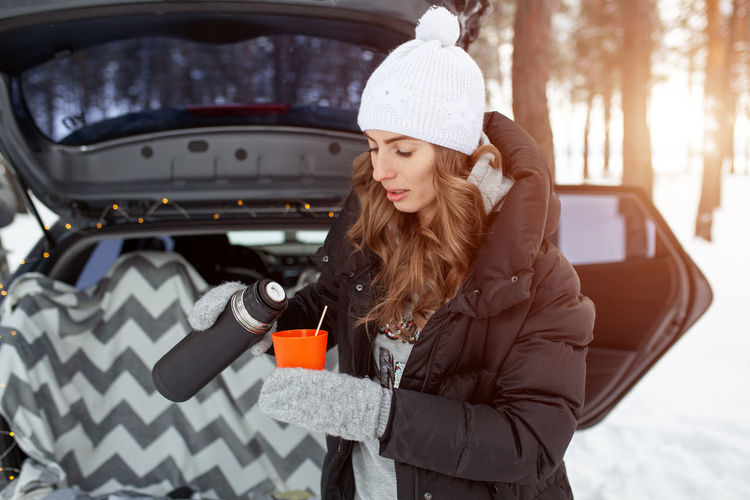 Young woman pouring drink in glass while standing against car in forest during winter