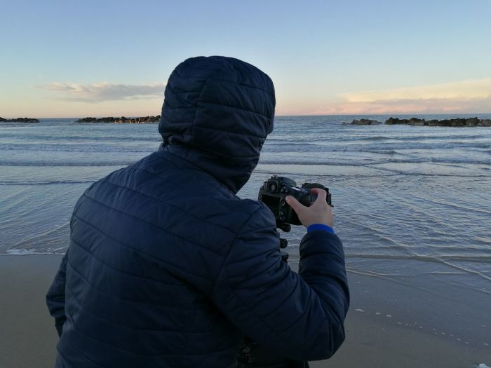 Rear view of man photographing at beach during sunset