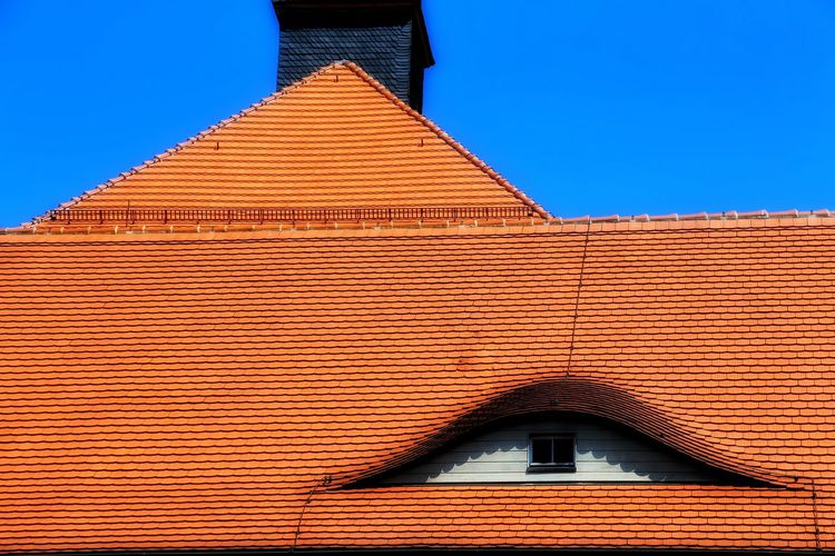 High section of roof against clear blue sky