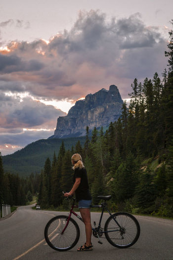Woman with bicycle on road against mountains at dusk