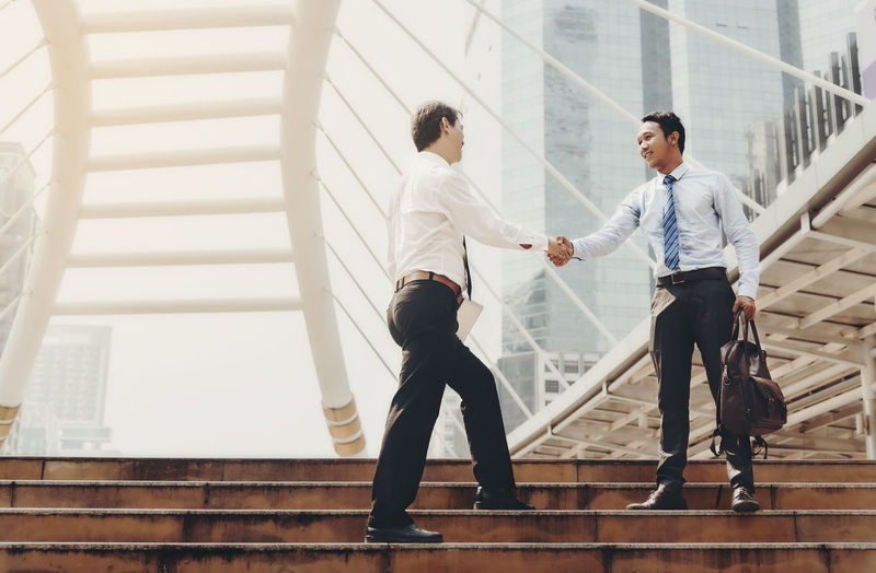 Businessmen are handshake to agree to join the business. The same team in the big city. Adult Architecture Built Structure Business Business Person Businessman Coworker Full Length Handshake Indoors  Males  Men Occupation Railing Real People Staircase Standing Steps And Staircases Togetherness Two People Well-dressed Young Adult Young Men