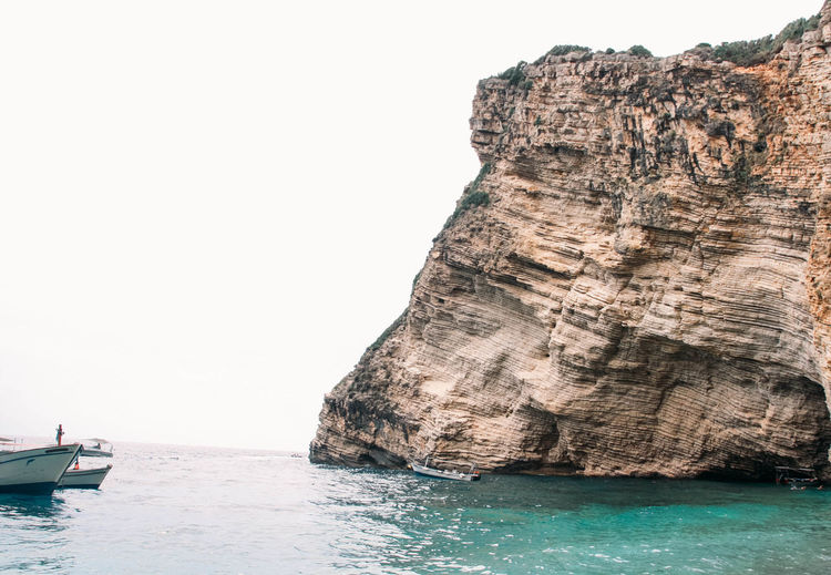 Scenic view of rock formation in sea against clear sky