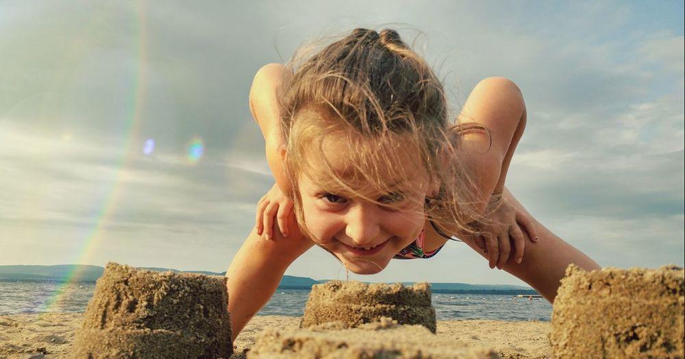 Portrait of girl over sandcastle at beach against sky