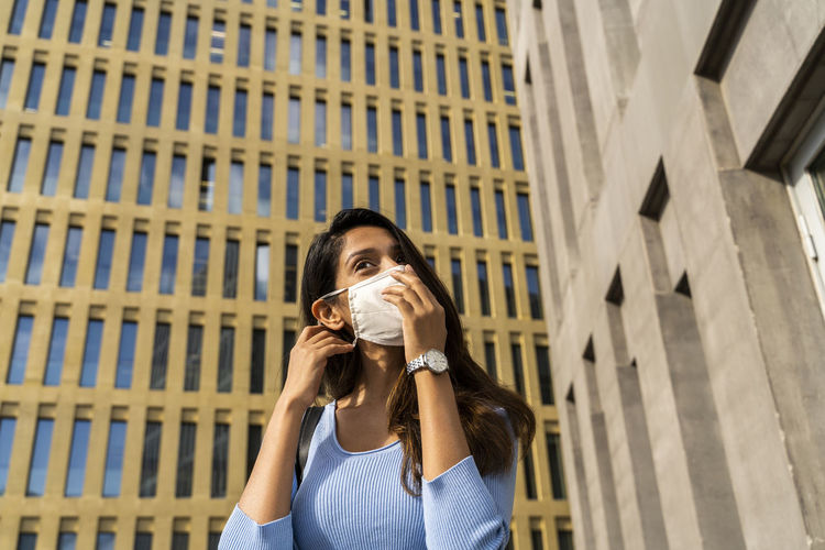 Portrait of beautiful young woman drinking glass against building in city